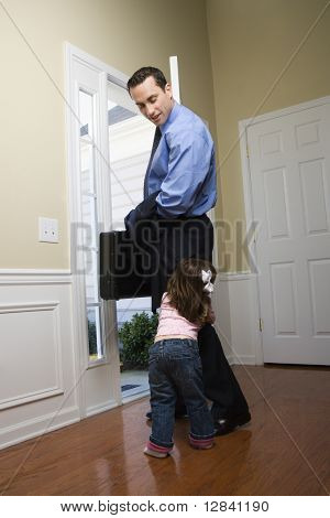Caucasian businessman   at open door with briefcase with daughter tugging on his leg.