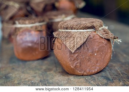 Abkhazia wild honey in Clay pot with cloth  on wooden background
