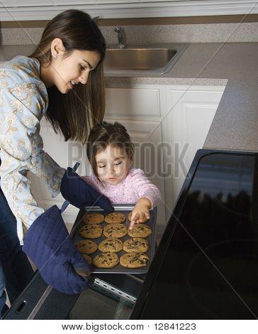 Caucasian Mother and Daughter Cookies aus dem Ofen nehmen.