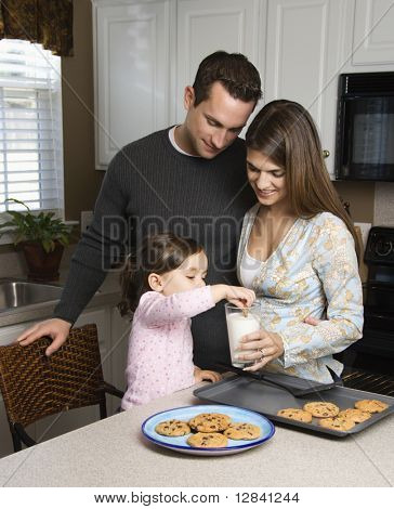 Caucasian mother and father with daughter eating cookies and milk.