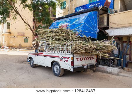 ASWAN, EGYPT - FEBRUARY 5, 2016: Toyota pickup truck with sugar cane in front of the store.