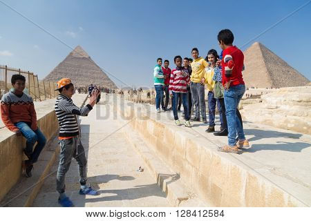CAIRO, EGYPT - FEBRUARY 1, 2016: Local boys taking photos of group of kids in front of the Great pyramid of Giza.