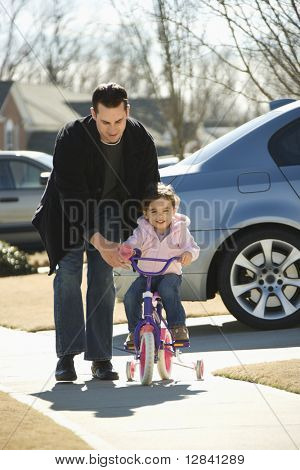 Caucasian father helping daughter ride bicycle.