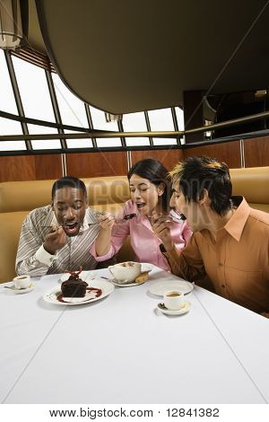 Small group of mid adult friends eating dessert at a restaurant.