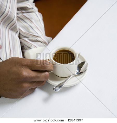 African American male hand holding handle of expresso cup.