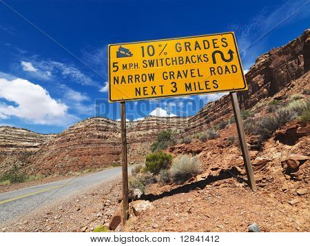 Road sign warning steep grade in Utah mountainous area.