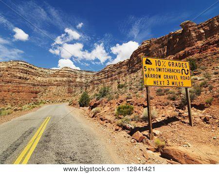 Road sign warning steep grade through rocky Utah landscape.