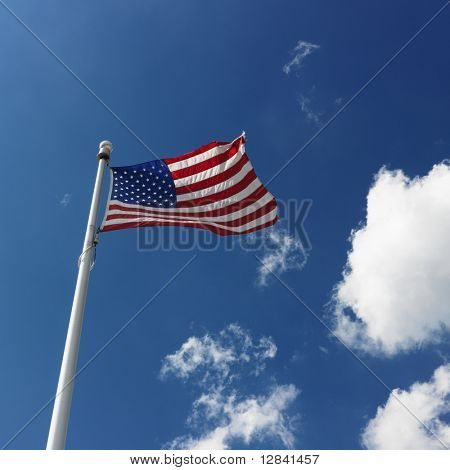 Low angle view of American flag flying with cumulus cloud formation in blue sky.