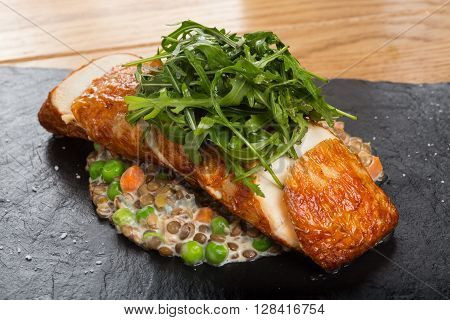 Fried chicken roll with lentils, fresh peas, carrots and gravy, garnished arugula on a black stone plate and a wooden countertop.