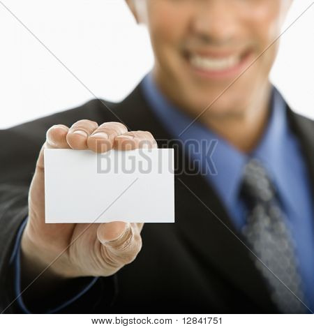 Caucasian middle aged man holding business card toward viewer.