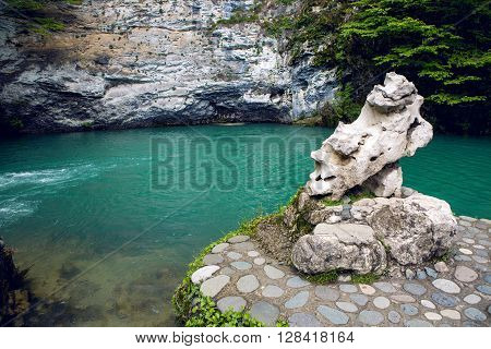 small mountain lake with green surface at the rock in Abkhazia in the spring with trees and the forest