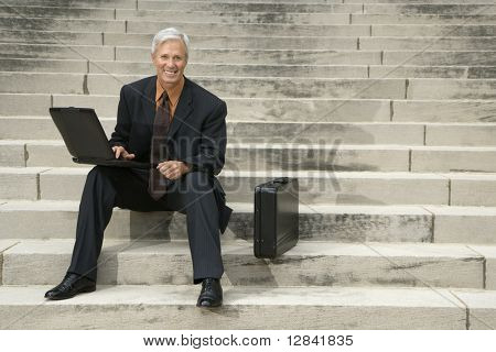Caucasian middle aged businessman sitting on steps outdoors with laptop and briefcase smiling at viewer.