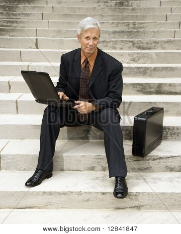 Caucasian middle aged businessman sitting on steps outdoors with laptop and briefcase looking at viewer.