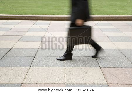 Motion blur of businessman legs walking outdoors with briefcase.
