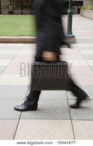 Motion blur of Caucasian businessman walking outdoors with briefcase.