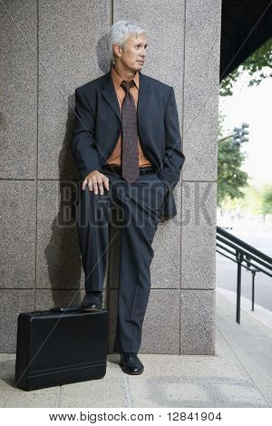 Caucasian middle aged businessman leaning on wall outdoors with foot on briefcase.