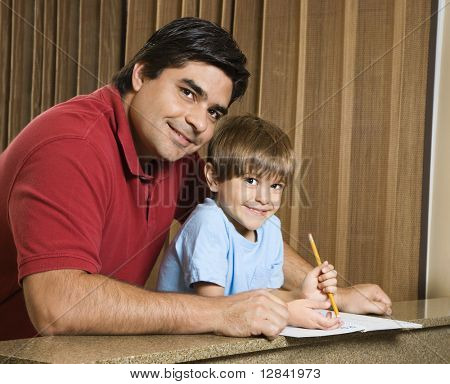 Hispanic father and son smiling at viewer with homework.