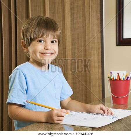 Hispanic boy smiling at viewer and doing homework.