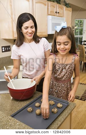 Hispanic mother and daughter in kitchen making cookies.