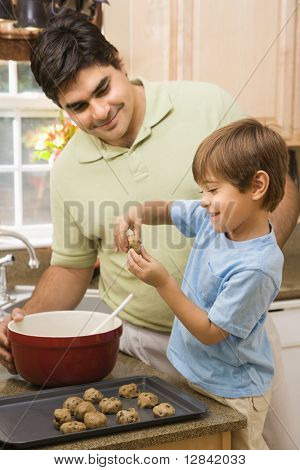 Hispanic father and son in kitchen making cookies.