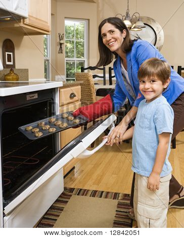 Hispanic mother and son putting cookies into oven and smiling at viewer.