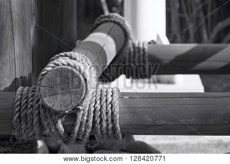 of monochrome color a closeup fragment of a design from wooden logs is fastened by a rope