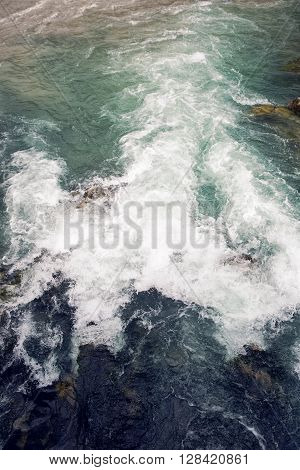 the turbulent water in the river with stones in Abkhazia in the morning
