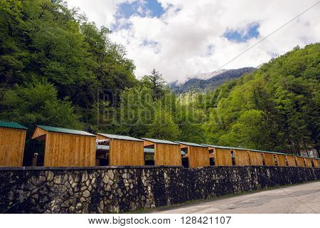small houses in mountain green forest with clouds in the sky in Abkhazia in the spring