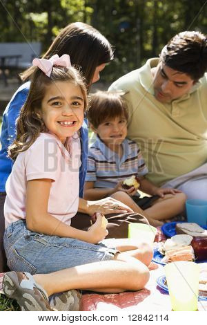 Hispanic girl smiling at viewer with family picnicing in the park.