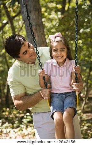 Hispanische Vater Tochter auf Schaukel schieben.