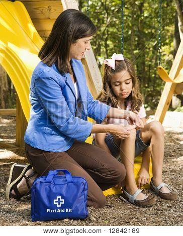 Hispanic girl sitting on playground slide while woman applies first aid bandage to knee.