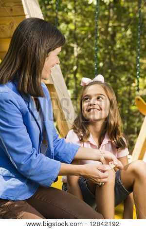 Hispanic girl sitting on playground slide smiling at woman applying first aid bandage to knee.