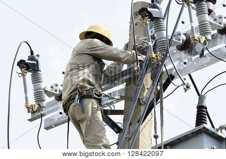 One electrician repairing wire on electric power pole.