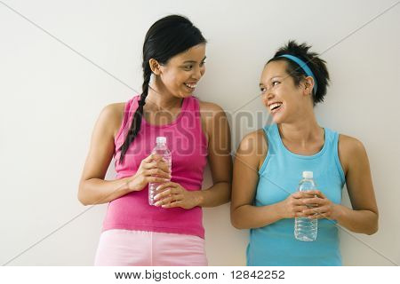 Two young women standing in workout clothes talking and smiling holding bottled water.