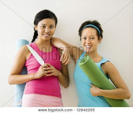 Two young women standing in workout clothes holding yoga mats and smiling.