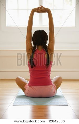 Rear view of young woman sitting on mat with legs crossed stretching.