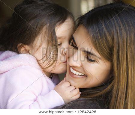 Caucasiano, mãe de uma filha de exploração beijando sua bochecha e sorrindo.