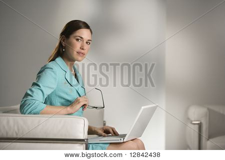 Caucasian mid adult professional business woman sitting in modern office working on laptop computer holding eyeglasses and looking at viewer.