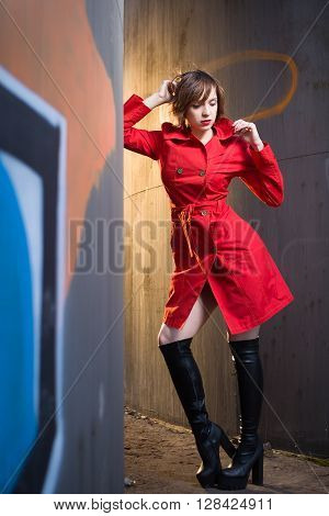 Attractive young woman alluring in sexual lingerie and red coat at grunge industrial setting at sunset. Beauty, fashion. Concept: seduction, exhibitionism.