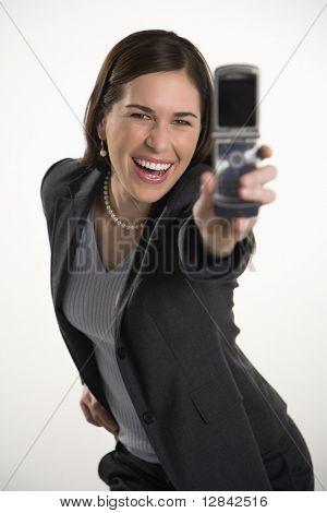 Caucasian mid adult professional business woman taking picture of self with camera phone and smiling.