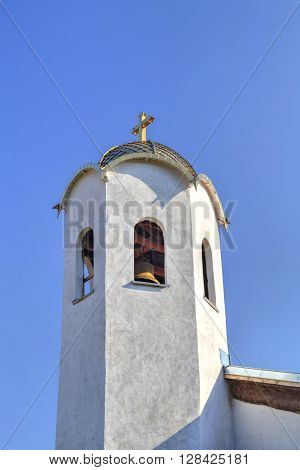 Church steeple with a cross on blue sky