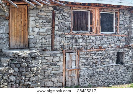 Unfinished stone house with wooden door and windows closeup