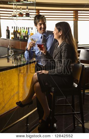 Young adult Hispanic couple toasting at bar.