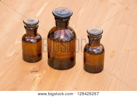 Small brown glass bottles on wooden board