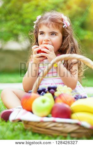 Portrait of a cute little girl sitting on the green grass field in a park and with pleasure eating tasty juicy apple, healthy babies nutrition