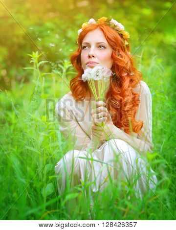 Portrait of a beautiful girl wearing floral wreath on red curly hair, enjoying spring grass field, holding in hands bouquet of dandelion flowers and dreamy making a wish