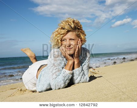 Attractive young blond woman lying in sand on Maui, Hawaii beach with head resting on hands.