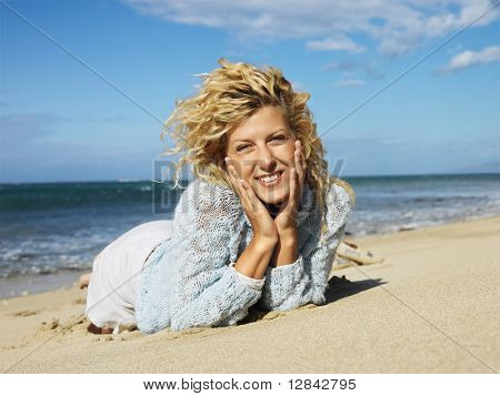 Pretty young blond woman lying in sand on Maui, Hawaii beach with head resting on hands smiling.