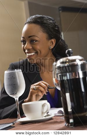 African American businesswoman smiling and sitting at table in restaurant.