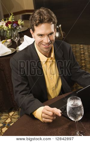 High angle view of Caucasian businessman with laptop in restaurant.